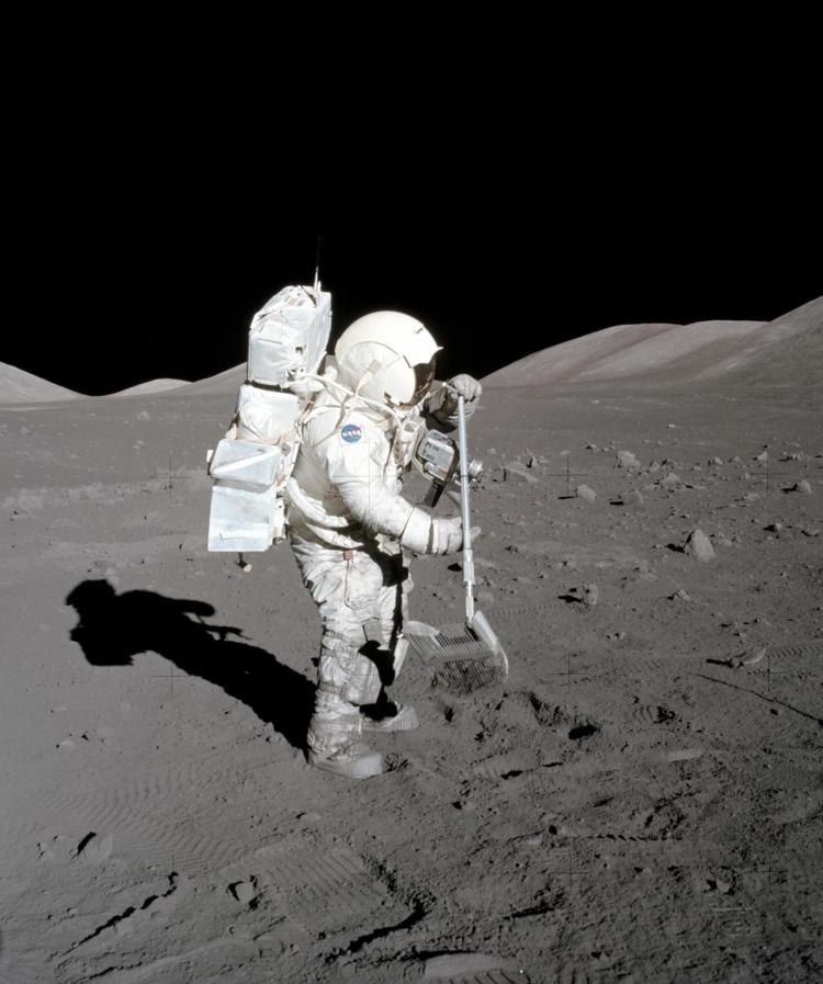 "Harrison Schmitt collects geologic samples from the surface of the moon using a ""lunar rake."""