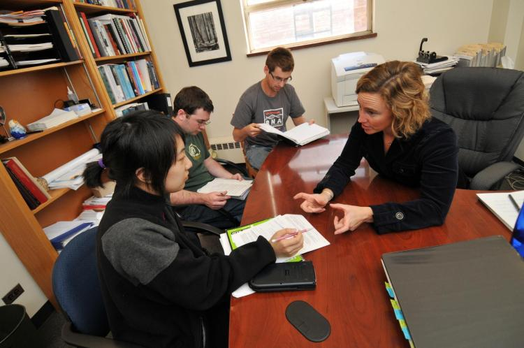 Biochemistry Professor Amy Palmer works with three students in her office