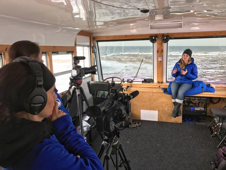 Student filming on a boat in the arctic