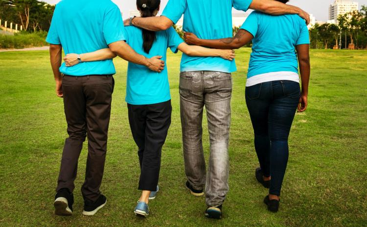 Group of people walk arm in arm