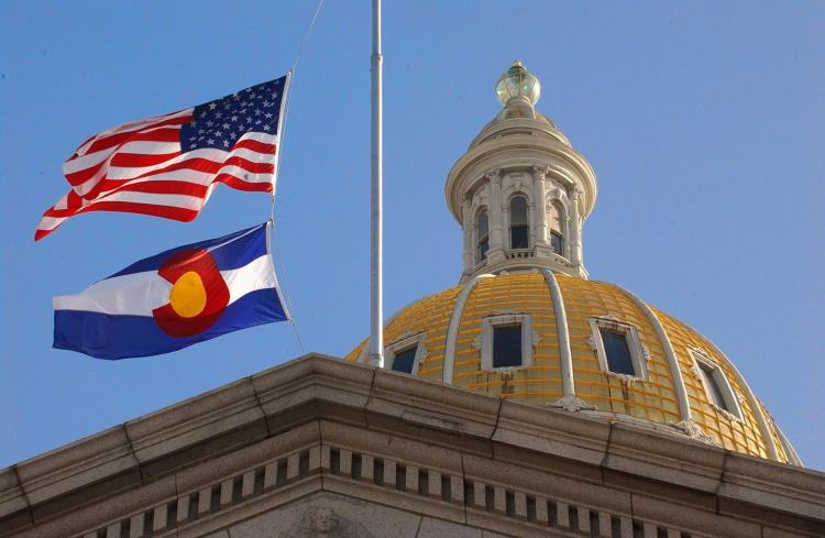 The American flag and the Colorado flag blowing in front of the state capitol dome.