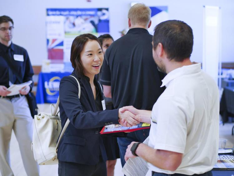student shakes hands with employer at last years just in time career fair
