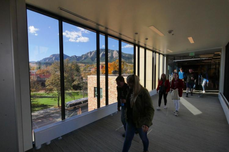 Campus community members walk through CASE building near panoramic window