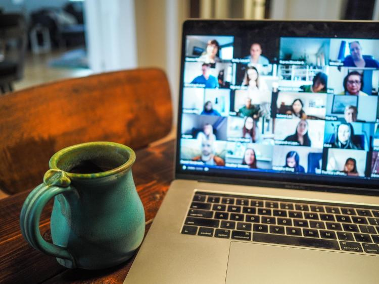 coffee mug and Zoom conference on laptop