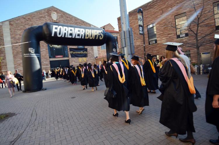 Graduates walk under ForeverBuffs arch during commencement