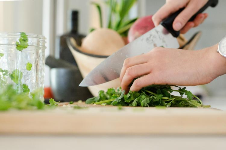 Person cutting up cilantro in kitchen