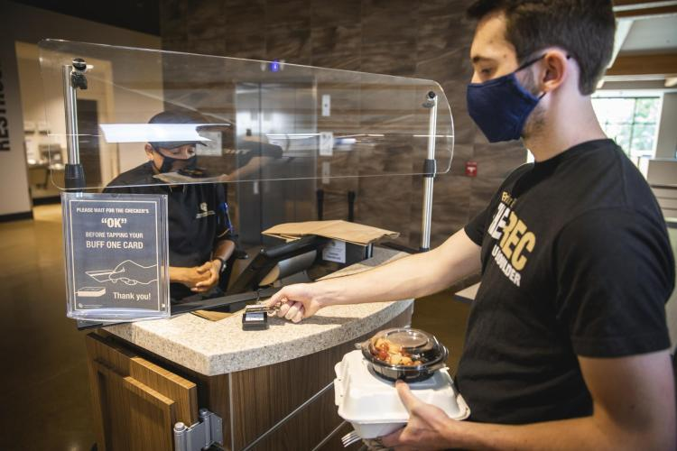 Person wearing a mask being served food in dining hall.