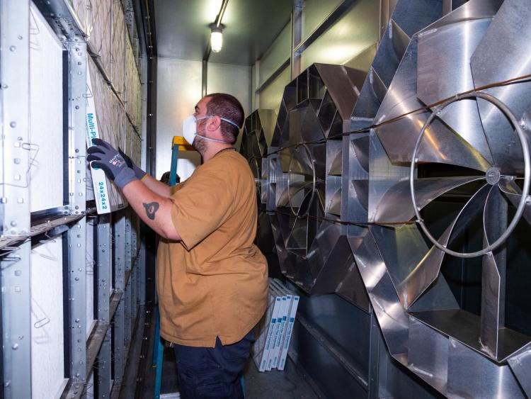 A maintenance worker installs new air filters in a ventilation system.