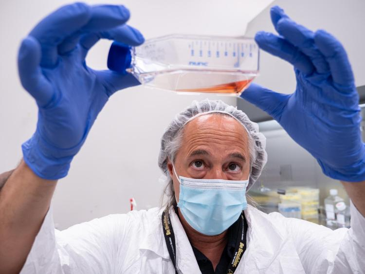 Mark Hernandez, wearing protective gear, inspects a flask filled with liquid