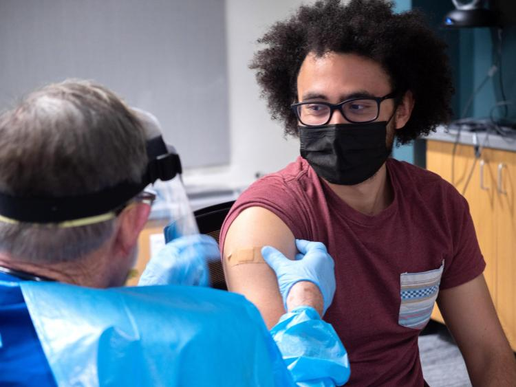 Student gets a vaccine from a doctor wearing a gown and face protection