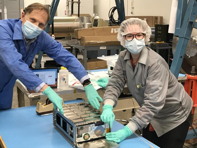 Rick Kohnert, project manager for CUTE, and Arika Egan pose with the small satellite at LASP.