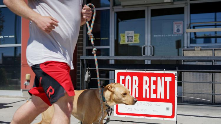 A business displays a 'For Rent' sign in Denver, Colorado.