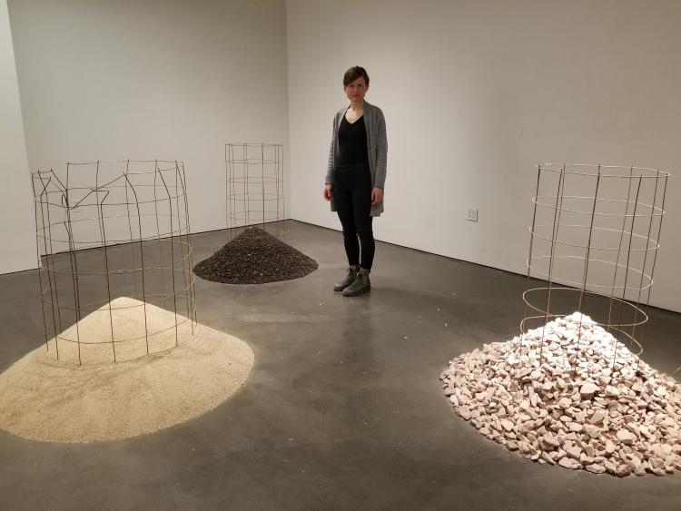 Elspeth Schulze standing among piles of sand, chopped up asphalt and granite