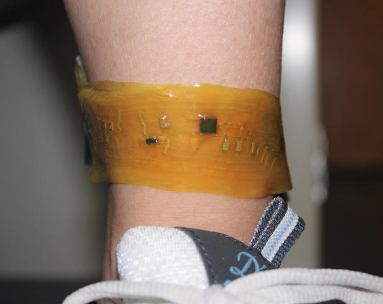 "A person wears an ""electronic skin"" device on the ankle."