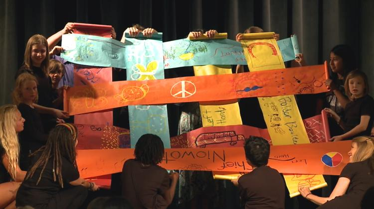 Children hold banners 'weaving together the fabric of community'
