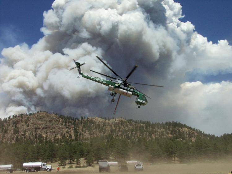 A helicopter flies over the Hayman fire