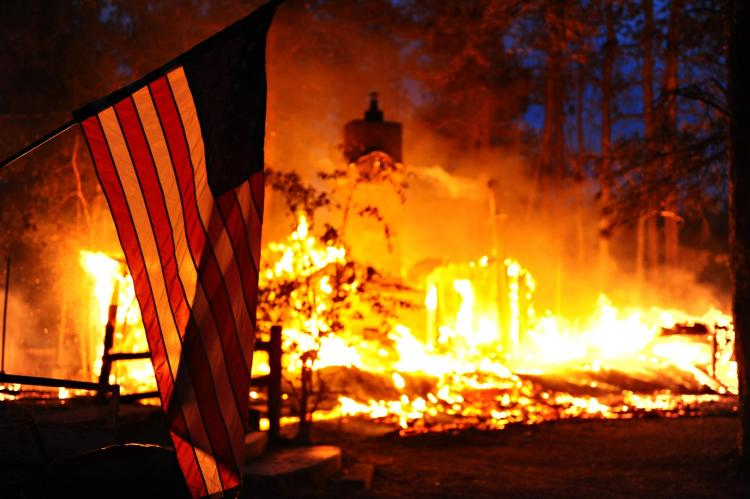 Wildfire destroys home, American flag in foreground