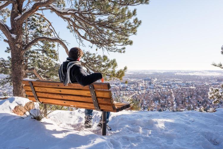 Man sits on bench at snowy Flagstaff Lookout, looking out over Boulder
