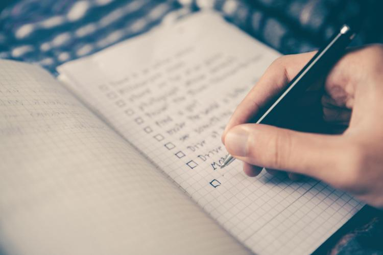 person writing a to-do list