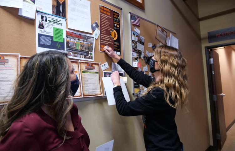 Women post educational materials to a bulletin board.