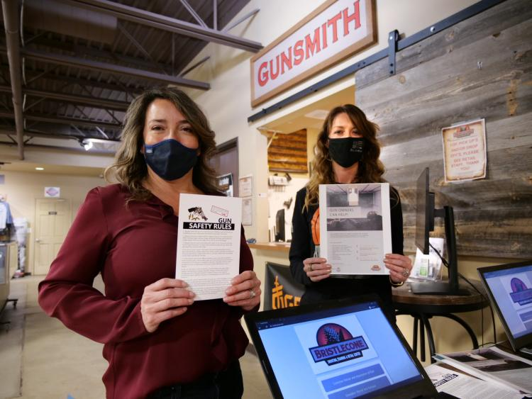 Two women hold up educational materials near a cash register
