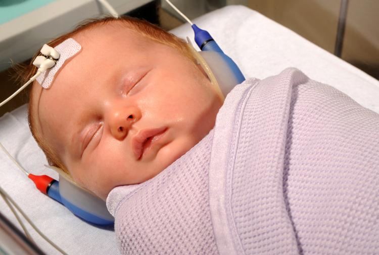 Infant having hearing test