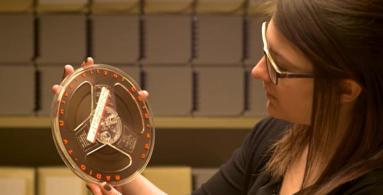 CU Boulder archivist Jane Thaler looks at a tape of a 1961 plenary talk by Henry Kissinger.