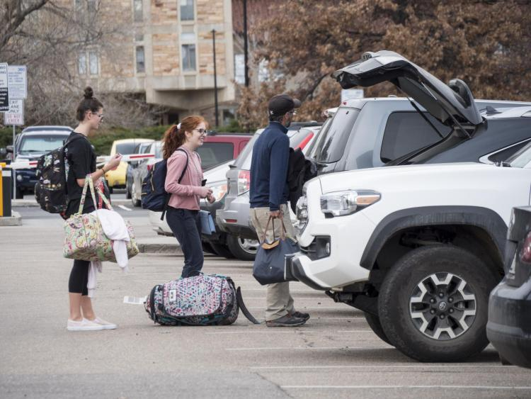parent helps students load their bags into a car for break