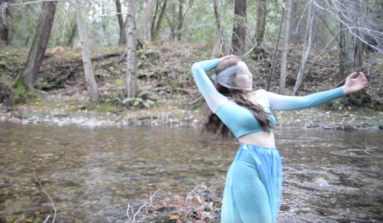 Rae Lewark performing near creek