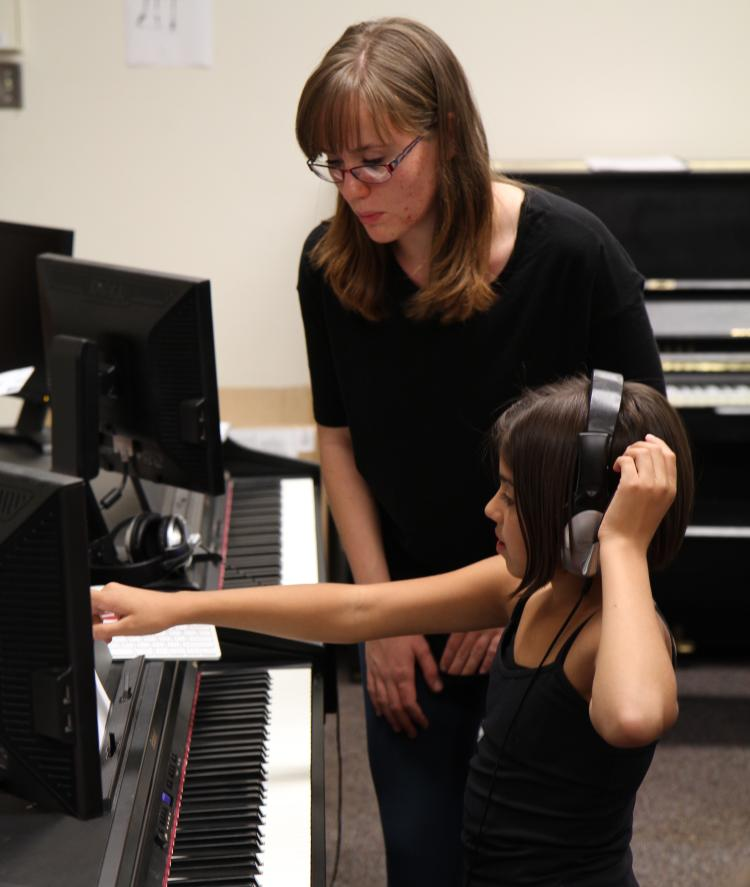 CU student teacher helps elementary student during Piano for Dreamers class