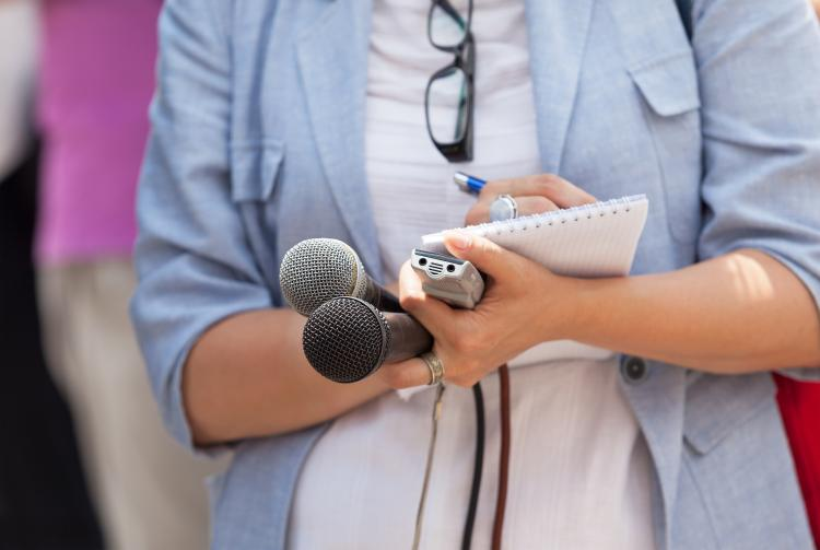 In a stock image, a journalist stands with two microphones, a reporter's notebook and pen.