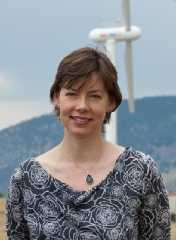 Julie Lundquist portrait with a faded wind turbine behind her and a out of focus hill behind that.