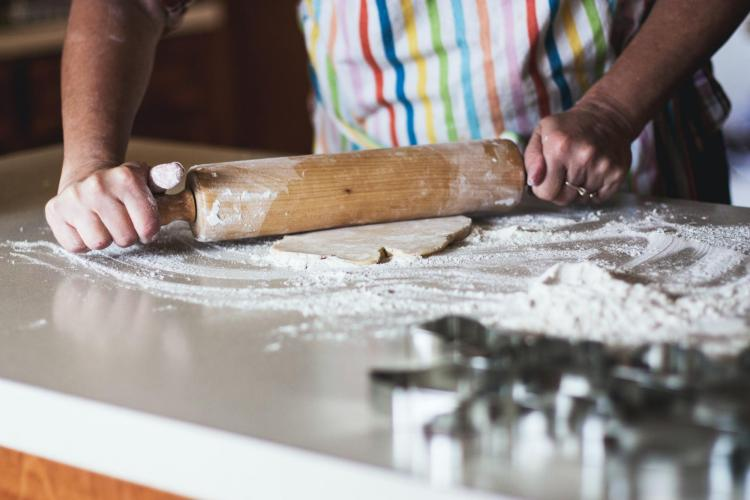person rolling dough with rolling pin