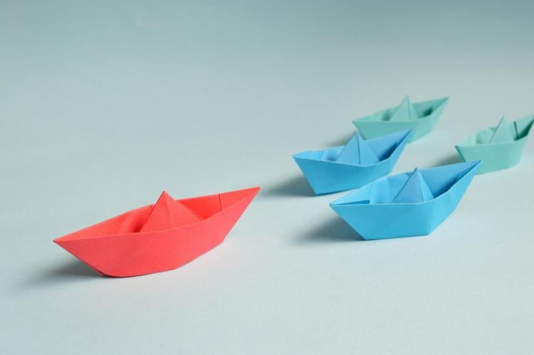red paper boat leading other paper boats