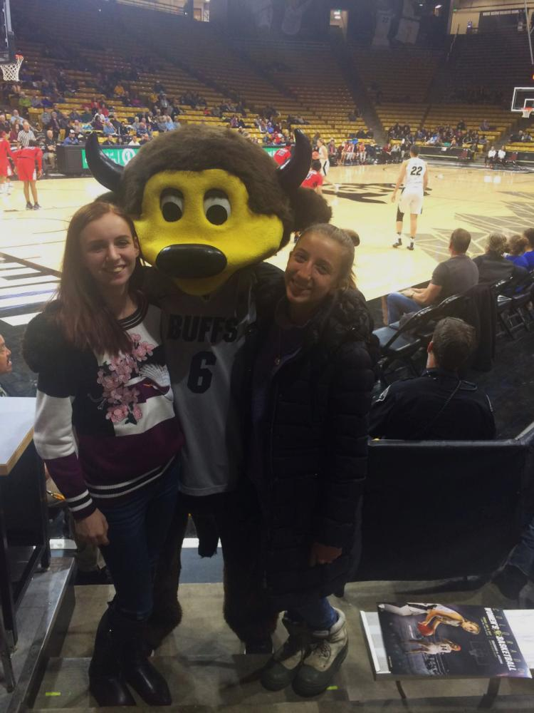 Bara, right, and a friend pose for a photo with Chip at a Buffs basketball game