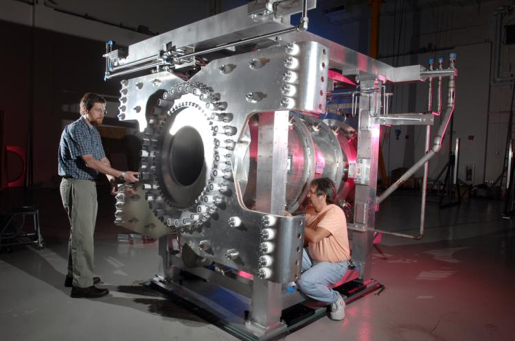 "Eric Zimmerman (left) and a colleague work on a ""magnetic horn,"" a device that helps the T2K experiment generate neutrino beams."