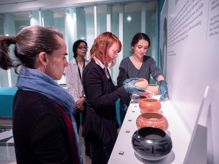 Museum staff get ready a display of bowls