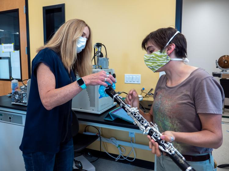 Shelly Miller (left) and graduate student Teyha Stockman (right) fit a bell cover over a clarinet.