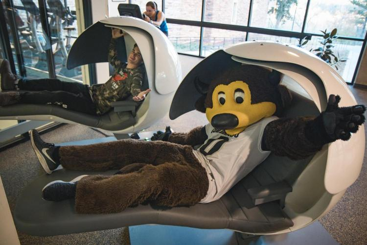 Chip and student pose for photo in nap pods on campus