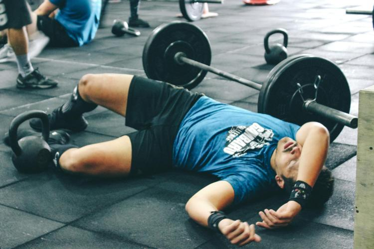 Person lies on gym floor, exhausted after lifting weights