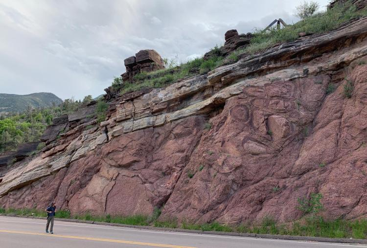 A hiker walks past one site of the Great Unconformity near the town of Manitou Springs, Colorado.