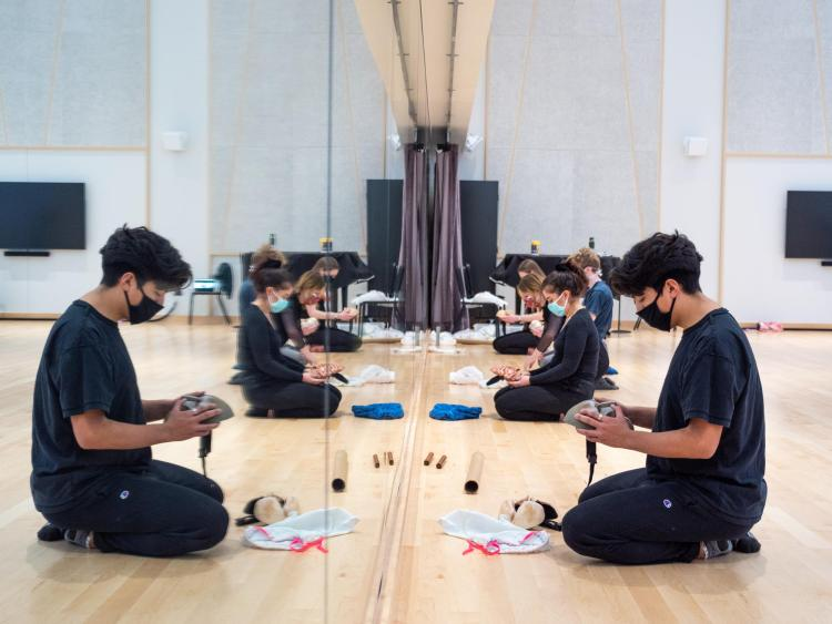Student examines a mask while sitting in front of a mirror in a dance studio
