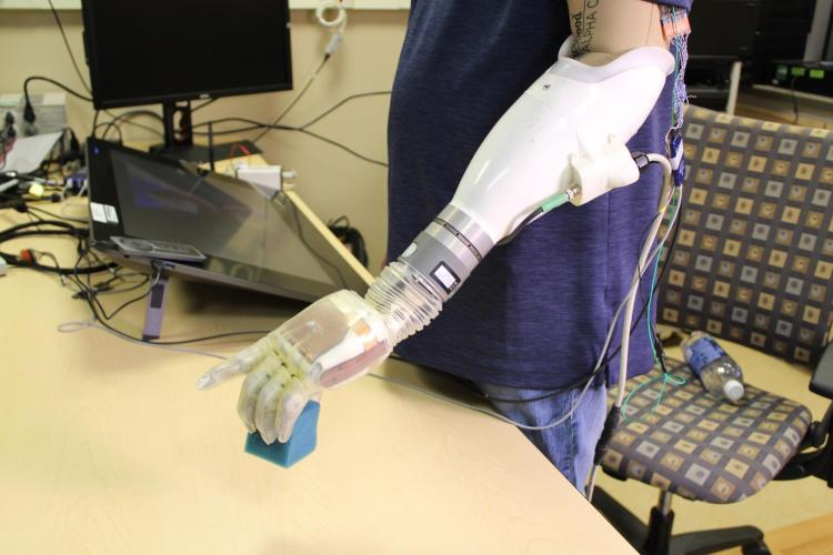 A human subject lifts a block using a feeling prosthetic.