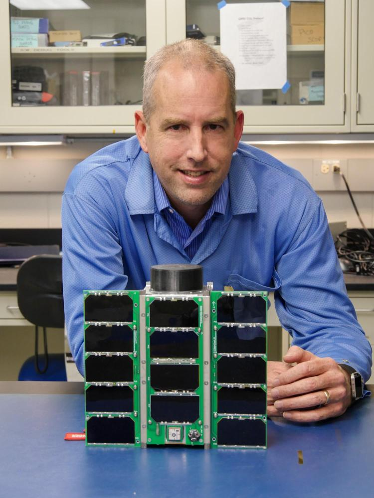 Scott Palo with a small satellite known as a CubeSat