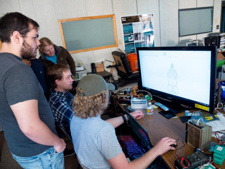 Engineering students gather round computer monitor