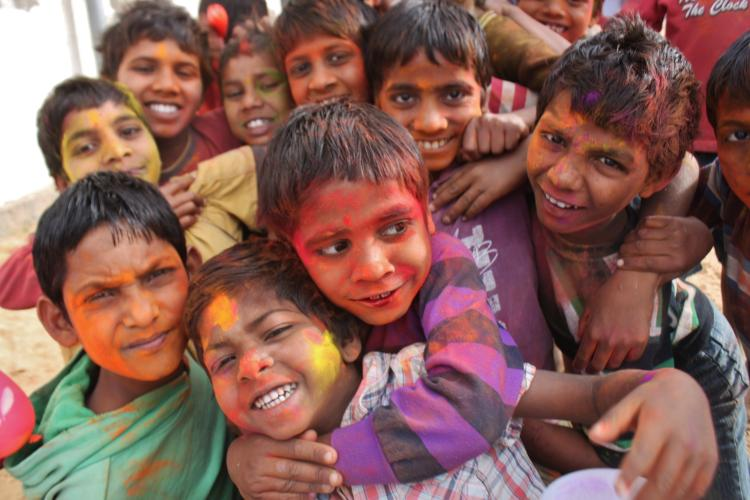 10 Kids in India with paint on their faces. Two in the front are hugging.