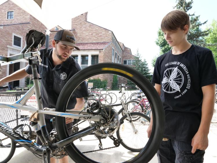 Max Robbins, a senior environmental science major from Grand Junction (left) and Thrombin Atwell-Donaghey, a sophomore chemistry major from Boulder tune a bike at the UMC bike station at the University of Colorado Boulder.