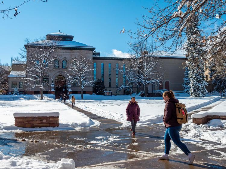 Students walk across a snowy campus