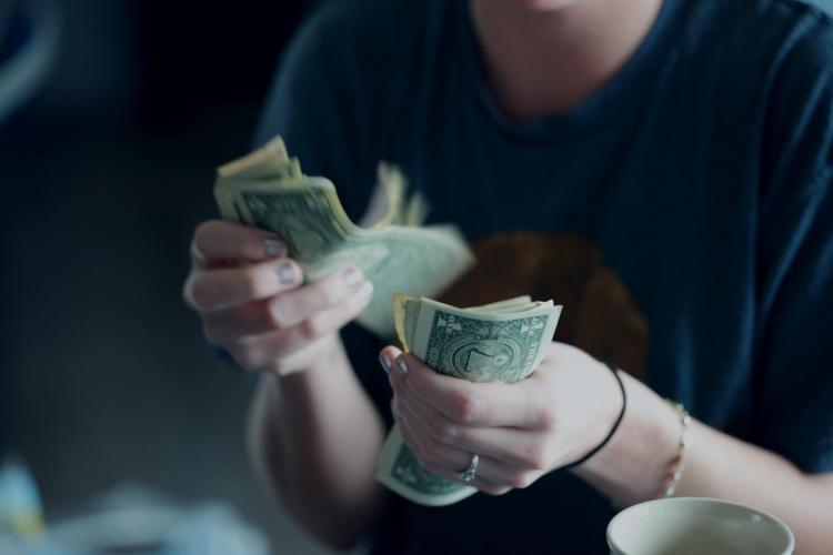 Person counting dollar bills