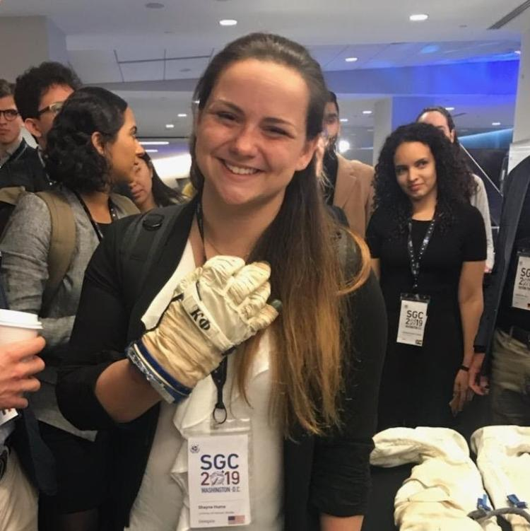 Shayna Hume wearing a spacesuit glove